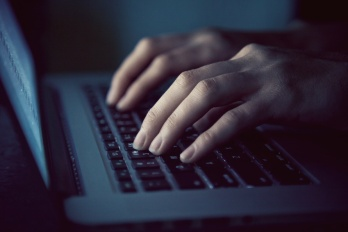 hands with laptop typing in night
